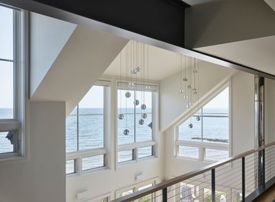 House on the Bluff Hero Interior Loft Water View Oceanfront Bubble Lights Steel Beam Modern Contemporary